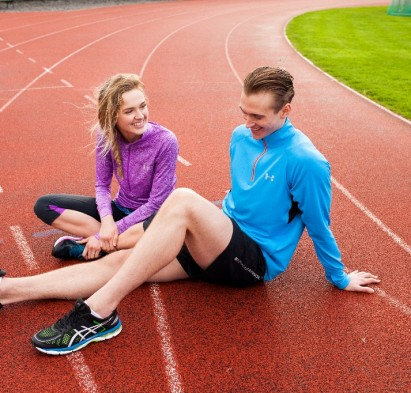 Guy and girl running track